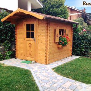 Casetta in legno in angolo di giardino a confine in prossimità di siepe